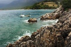 Small ship near the rocky shore Royalty Free Stock Photo