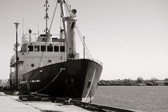 Small ship at the pier. Black and white image of a small research vessel anchored at the pier Stock Photography