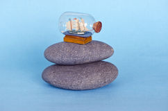 Small ship sailboat model in glass bottle on sea stone Royalty Free Stock Photography