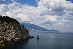 A small ship sailing through the blue sea against the background of huge mountains Stock Photo