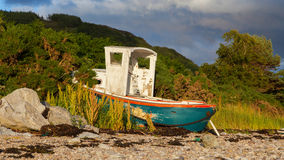 Small shipwreck at a loch with stone beach Stock Photography