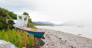 Small shipwreck at a loch with stone beach Stock Photo