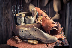 Small shoemaker workshop with shoes, laces and tools. On old wooden table Royalty Free Stock Photography