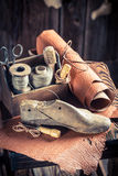 Small shoemaker workshop with tools, leather and shoes royalty free stock images