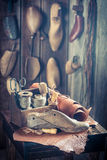 Small shoemaker workshop with tools, shoes and leather Stock Photos