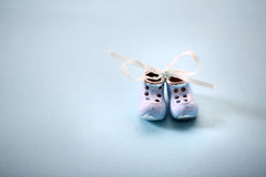 Small shoes. On the blue background Stock Images