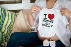Small shoes and a sweater with text for the unborn baby in the belly of pregnant woman, pregnant woman holding small baby shoes an stock photos