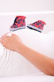 Small shoes for the unborn baby on the belly of pregnant woman Stock Photography