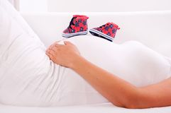 Small shoes for the unborn baby in the belly of pregnant woman Royalty Free Stock Photos