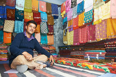 Small shop owner indian man at his souvenir store. Small shop owner indian man selling shawls, clothing and souvenirs at his store royalty free stock image