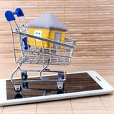 Small shopping basket cart with the house on tablet computer on background of wooden fence. stock photo