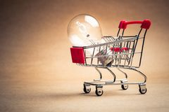 Small Shopping Cart and Ideas. Small shopping cart with glowing light bulb for shopping idea, smart buying or energy saving concept royalty free stock photo