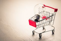 Small Shopping Cart and Ideas. Small shopping cart with glowing light bulb for shopping idea, smart buying or energy saving concept royalty free stock image