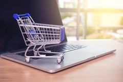Small shopping cart on Laptop for shopping online with sunny background, Technology business online concept. royalty free stock image