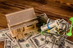 Small shopping cart with rolled up one hundred dollar banknotes and plywood model of the house on a wooden background. Loan, real. Small shopping cart with stock photography
