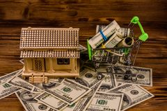 Small shopping cart with rolled up one hundred dollar banknotes and plywood model of the house on a wooden background. Loan, real. Small shopping cart with stock photos