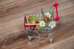 Small shopping cart with strawberries and flowers inside Royalty Free Stock Images