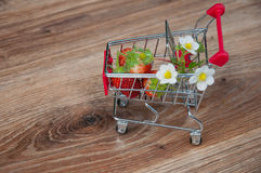 Small shopping cart with strawberries and flowers inside Stock Images