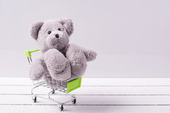Small shopping cart and a teddy bear. Conceptual image for sale of toys or children's fantasies Stock Images