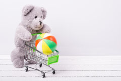Small shopping cart and a teddy bear. Conceptual image for sale of toys or children's fantasies Stock Photos