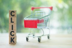 Small shopping cart and wooden blocks with click. Concept of online shopping application on a screen royalty free stock photo