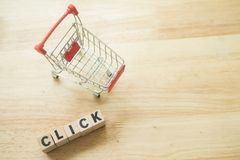Small shopping cart and wooden blocks with click. On wooden background. Concept of online shopping application on a screen royalty free stock photography