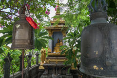 Small shrine at the Golden Mount in Bangkok. Golden Buddha statues and old bells at a small shrine at the Golden Mount at Wat Saket in Bangkok, Thailand Stock Image