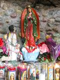 Small shrine of St. Mary filled with votive candles royalty free stock photos