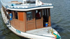 A small shuttle boat docks at a pier on Chao Phraya River. PAKKRET, NONTHABURI, THAILAND - JULY 2, 2015: A small shuttle boat docks at a pier on Chao Phraya stock footage