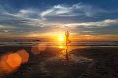 Small silhouette of a woman practicing yoga on sea beach Royalty Free Stock Images