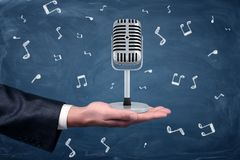 A small silver retro microphone standing on a businessman`s hand among music notes drawn on a blackboard background. Show business. Musical producer. Join stock image