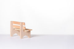 Small simple rustic wooden bench in a white room Royalty Free Stock Image