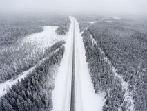 Small single car standing roadside in wintry road at blizzard, aerial view at straight northern route. Karelia, Russia royalty free stock photos