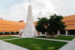 Small size of historic Stupa inside Thai temple in Bangkok. Small size Stupa surrounding by grass, tree and orange roof building inside Thai temple in Bangkok Royalty Free Stock Photography