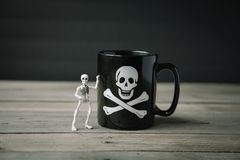 Small Skeleton Standing Beside Coffee Mug royalty free stock photography