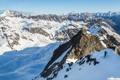 Small skier dropping into an icy peak above glaciers and snow in remote Alaska on a backcountry ski trip. A skier gets ready to drop into a steep, icy run above stock image