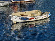 Small Skiff - Lyme Regis Harbour. Small skiff with reflections at Lyme Regis harbour on a calm autumn morning Stock Image