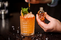 Small skull-shaped bottle, orange cocktail and barmen hand. Small skull-shaped bottle, orange mohito cocktail and barmen hand Royalty Free Stock Images