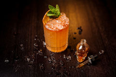 Small skull-shaped bottle and orange cocktail. Small skull-shaped bottle and summer cocktail with mint leaves and orange slice Stock Photos