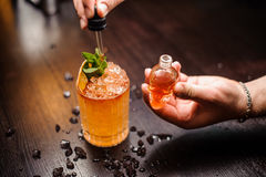 Small skull-shaped bottle, summer cocktail and barmen hand. Small skull-shaped bottle, orange cocktail and barmen hand Royalty Free Stock Image