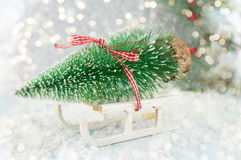 Small sleigh carrying a Christmas tree miniature Royalty Free Stock Image