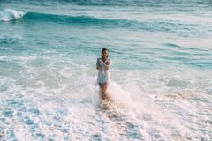A small slender girl in a beautiful white beach suit is standing in the blue water of the sea, knee-deep. Waves and. Splashes enveloped her body, arms crossed stock images