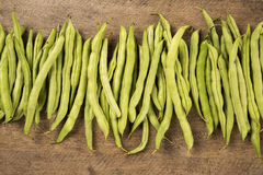 Small and slender green beans (haricot vert) on a wood. Fresh vegetable royalty free stock photography