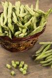 Small and slender green beans (haricot vert) on a wood. Vagens verdes em uma cesta de vime em uma madeira stock photo