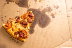 A small slice of pizza remaining in a large cardboard box with oil stains. Top view royalty free stock photos