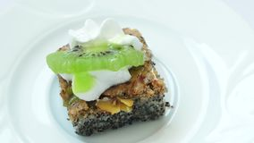 Small slice of poppy cake with kiwi and cream. stock video