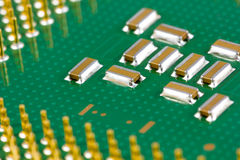Small smd capacitors on a processor. Macro picture of computer processor with small smd capacitors and golden pins Stock Image