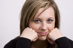 Small Smile. A gorgeous young woman rests her face on her hands and gives a small smile Royalty Free Stock Photos