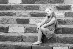 Small smiling baby girl in blue dress on colorful stairs Royalty Free Stock Photography