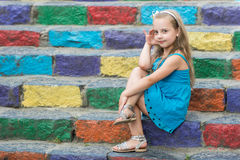 Small smiling baby girl in blue dress on colorful stairs Stock Image